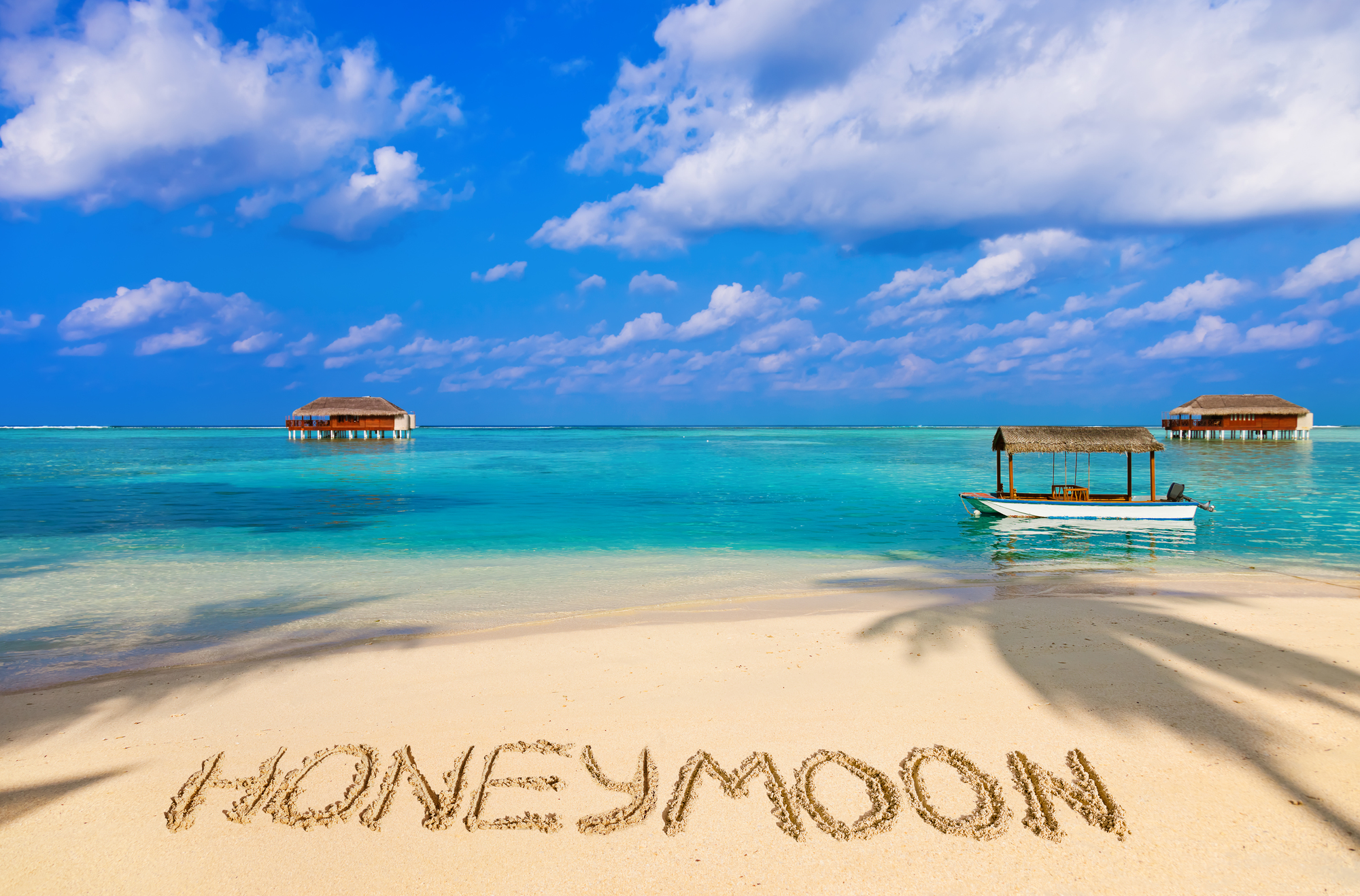 Word Honeymoon on beach - concept holiday background